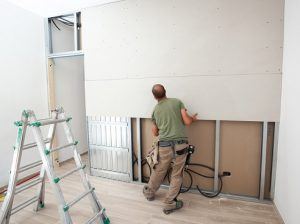 Worker building plasterboard wall. Working with cutting tools, fixing and measuring for drywall.